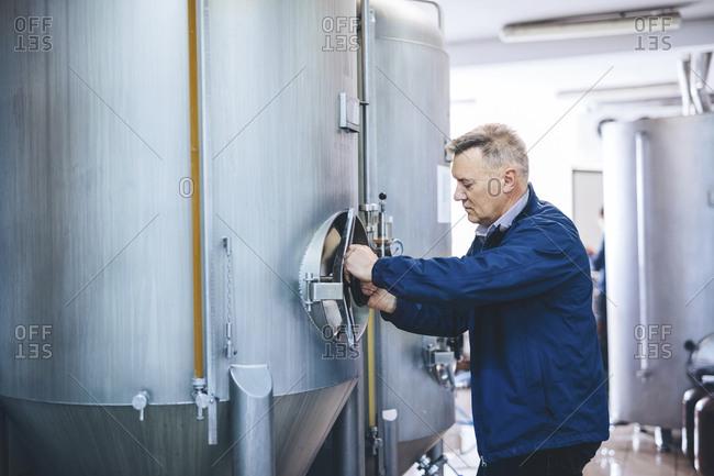 Side view of brewer adjusting handle of storage tank at microbrewery