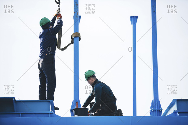 Manual workers working on machinery against clear sky at shipyard