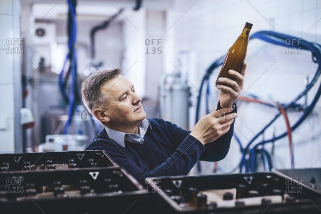 Brewer examining beer bottle while standing at warehouse