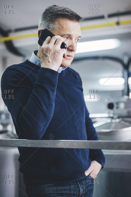 Brewer answering smart phone while standing at brewery