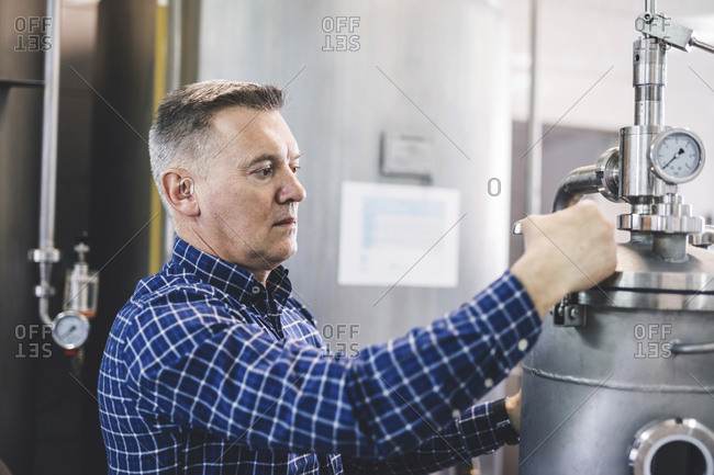 Brewer adjusting machinery while working at brewery