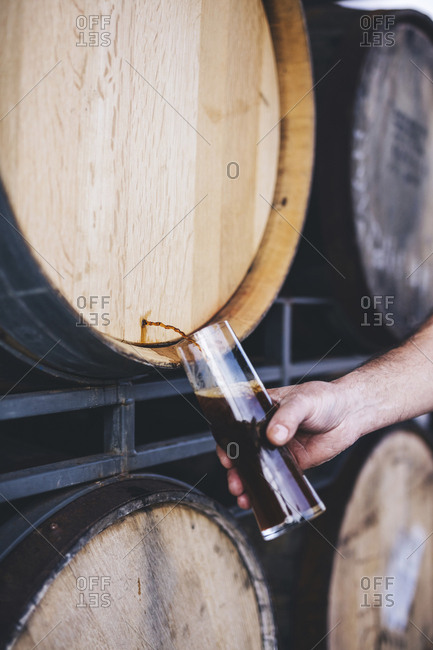 Cropped hand of brewer filling beer from barrel at warehouse
