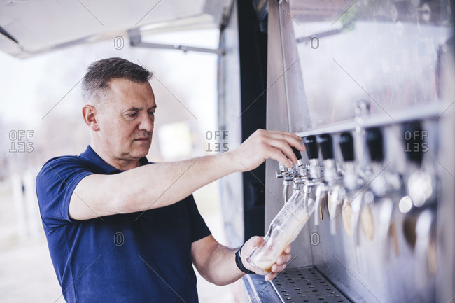 Brewer filling beer from tap while standing outdoors