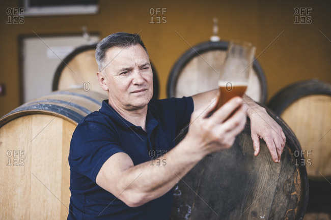Brewer looking at craft beer against barrels at warehouse