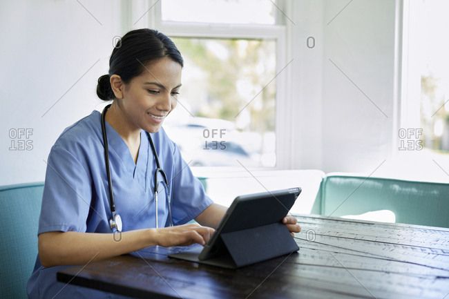 Smiling female doctor using tablet computer at table in hospital