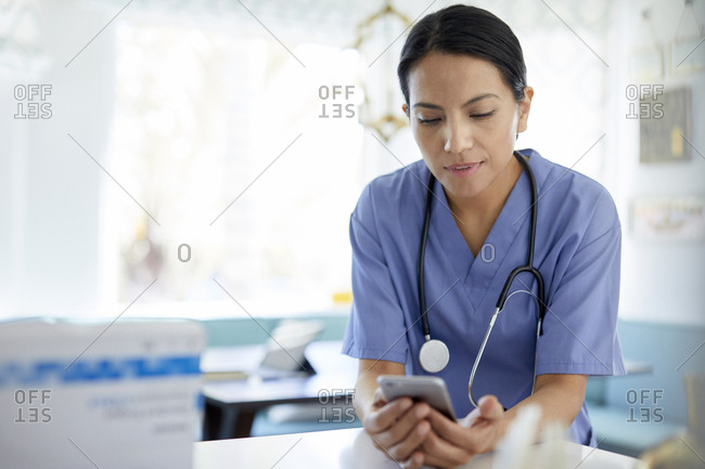 Female doctor with stethoscope using smart phone while working in hospital