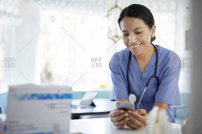 Smiling female doctor using smart phone while working in hospital