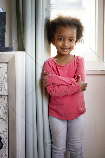 Portrait of smiling girl with arms crossed standing by curtain at home