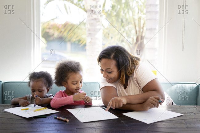 Cheerful mother pointing at paper with daughters against window at home