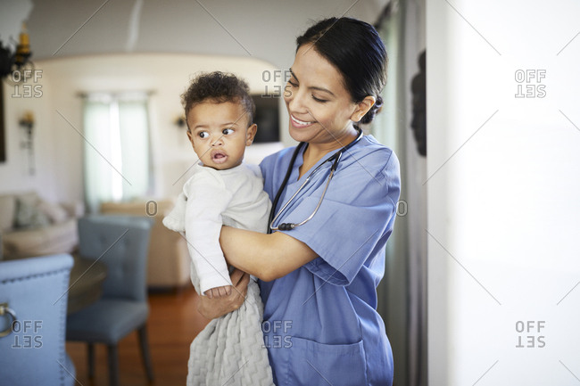 Smiling pediatrician carrying baby boy while standing at home