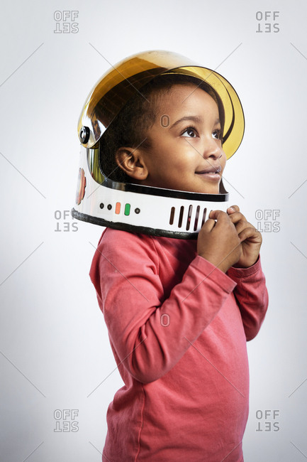 Thoughtful girl wearing space helmet while looking away against white background