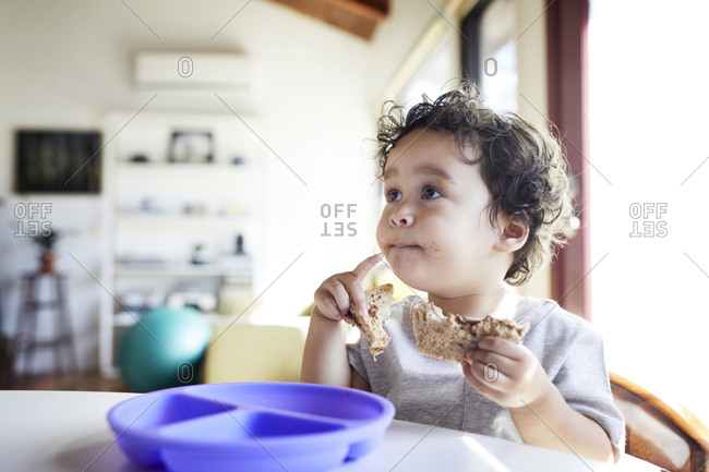 Close-up of cute baby boy holding breads while looking away at home