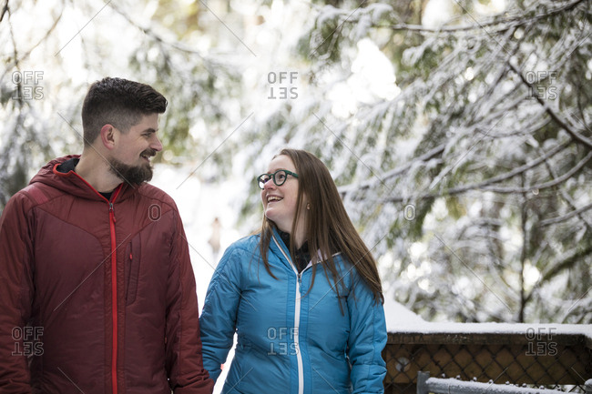 Smiling couple looking each other face to face while standing in forest at Lynn Canyon Park during winter