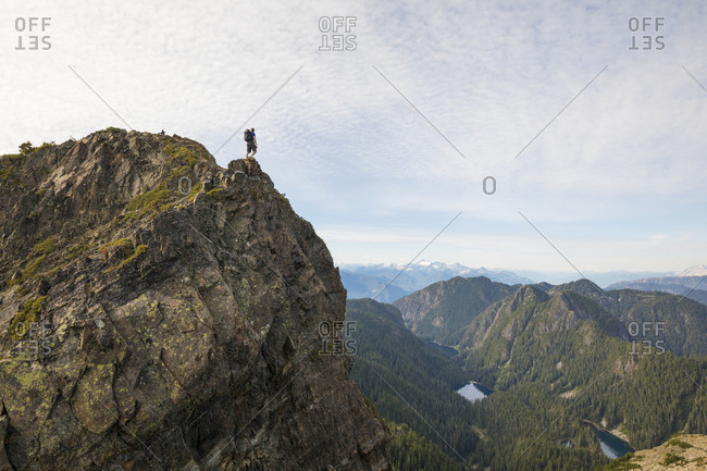 Mid distance view of hiker standing on cliff against sky