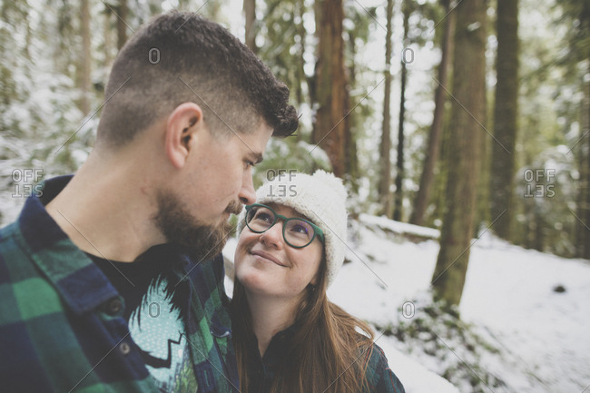 Close-up of loving couple looking each other face to face in forest at Lynn Canyon Park during winter