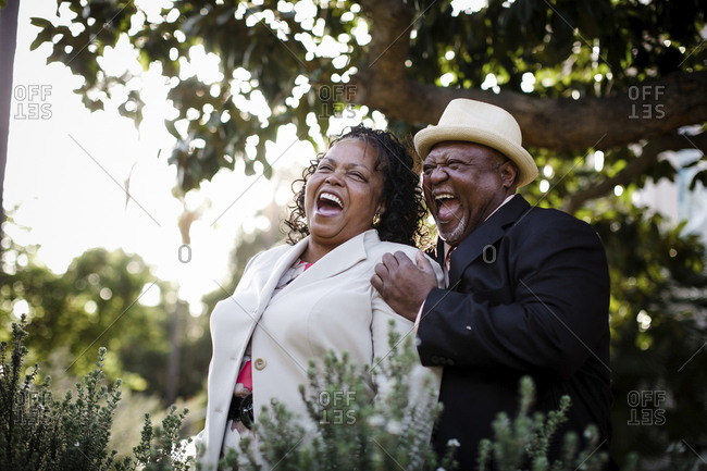 Happy senior couple laughing while standing at park