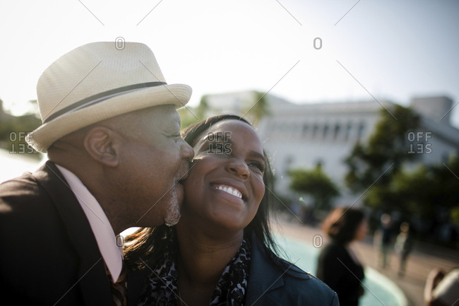 Close-up of happy father kissing daughter while standing against clear sky