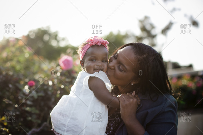 Happy mother kissing daughter while sitting by plants at park