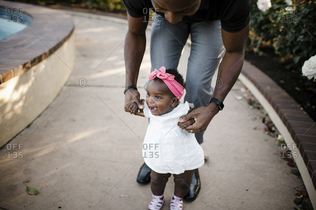Father assisting happy daughter in walking on footpath at park