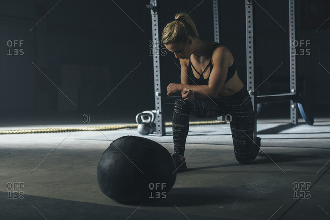 Female athlete exercising by fitness ball in gym