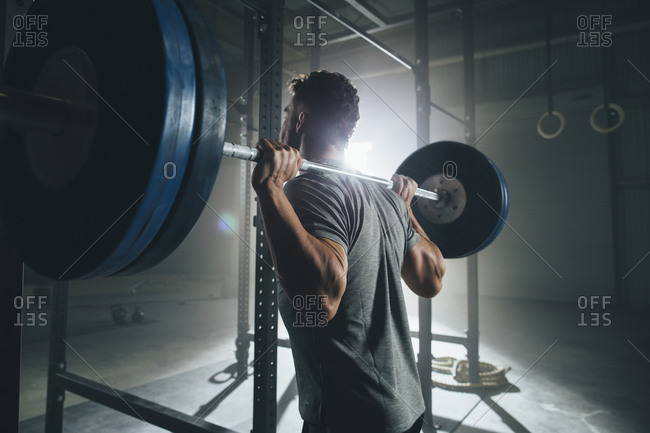 Side view of male athlete lifting barbell at health club