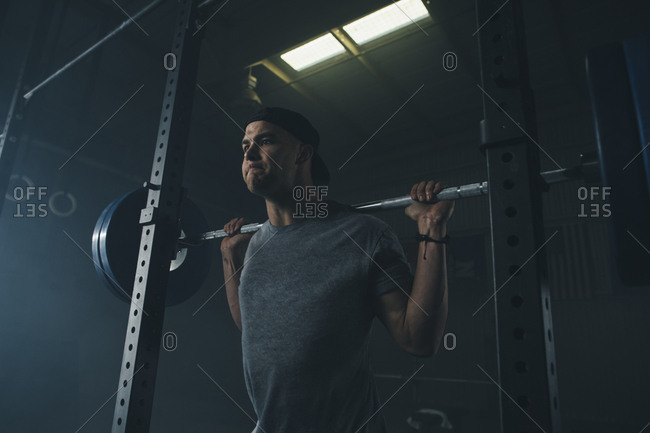 Low angle view of male athlete lifting barbell in health club