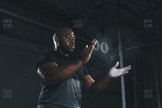 Low angle view of male athlete applying chalk on hands while standing in gym