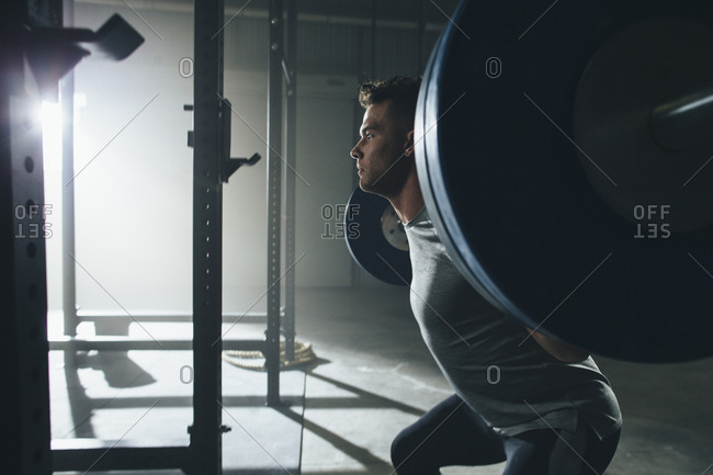 Side view of male athlete looking away while lifting barbell at gym
