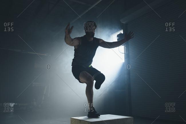 Adaptive athlete exercising on box in gym