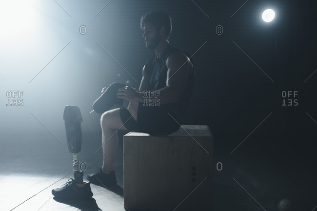 Adaptive athlete adjusting prosthetic equipment while sitting on box in gym