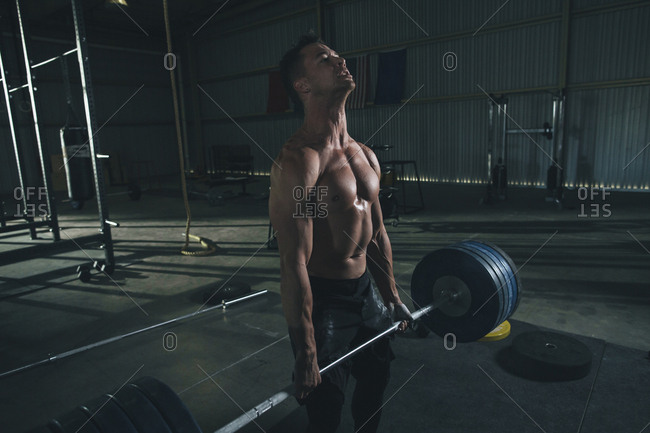 Shirtless male athlete lifting barbell in health club