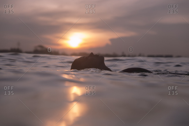 Carefree young woman swimming in sea against sky during sunset