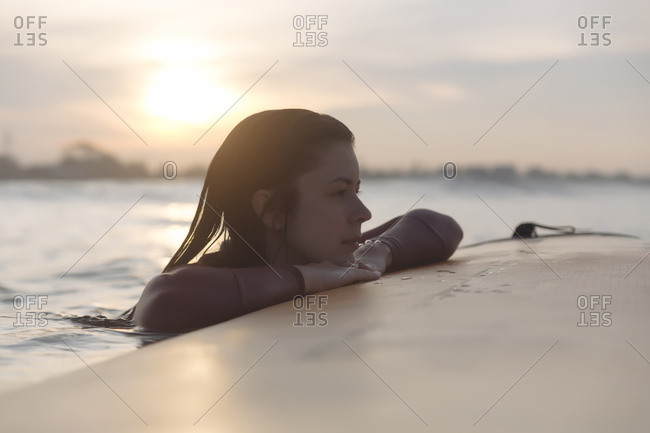 Thoughtful young woman leaning on surfboard while looking away in sea against sky during sunset