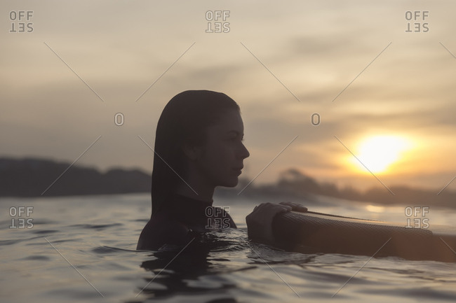 Thoughtful young woman with surfboard swimming in sea against sky during sunset