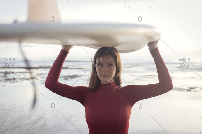 Portrait of young woman carrying surfboard on head while standing at beach