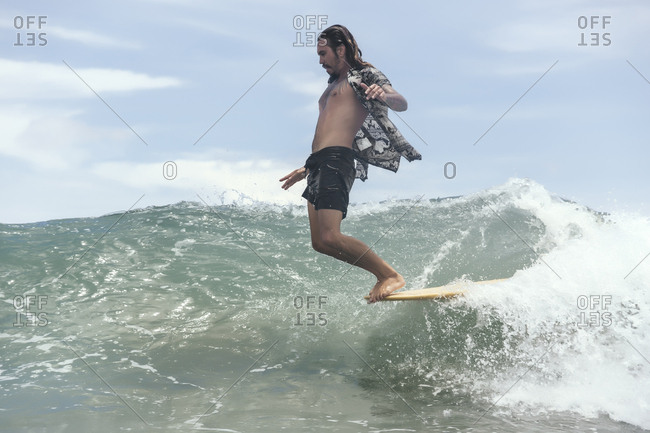 Man surfing while standing on surfboard's edge in sea against sky