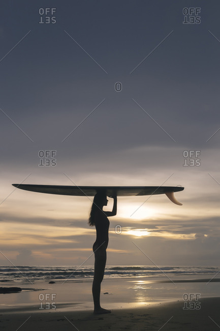 Side view of young woman carrying surfboard on head while standing at beach against sky during sunset