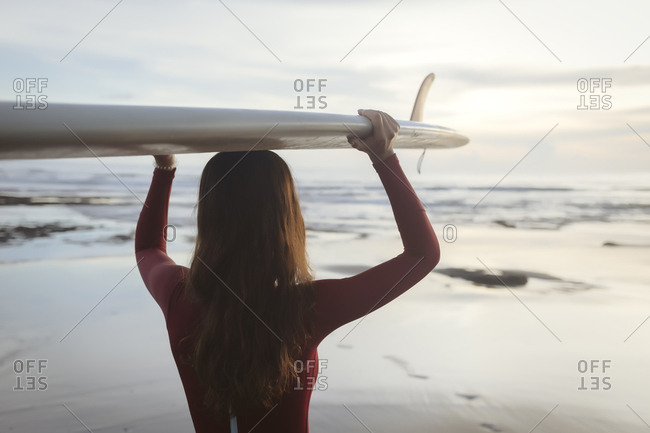 Rear view of young woman carrying surfboard on head while standing at beach
