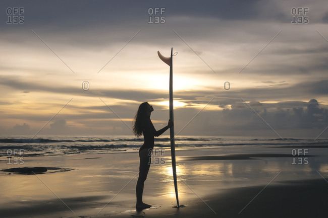 Side view of young woman with surfboard standing at beach against sky during sunset