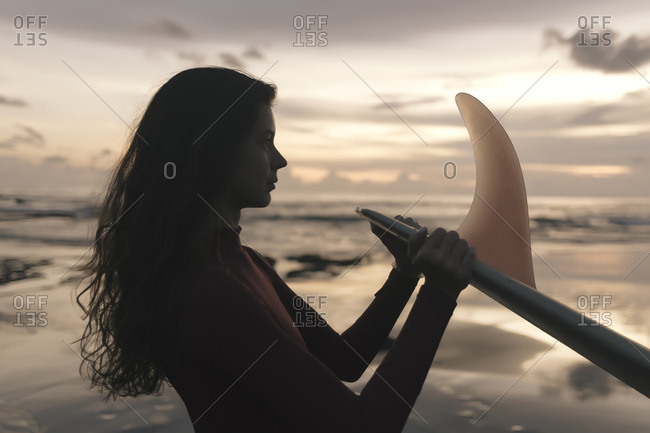 Side view of thoughtful young woman holding surfboard while standing at beach against sky during sunset