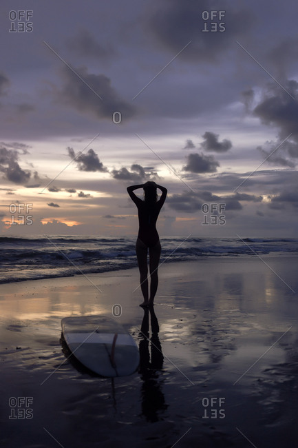 Full length of silhouette young woman with surfboard standing at beach against cloudy sky during sunset