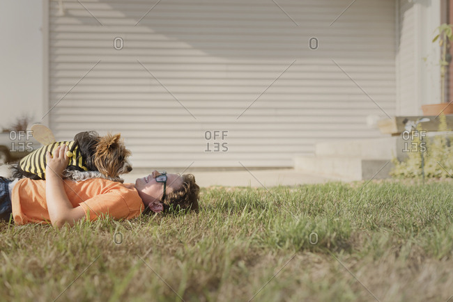 Side view of boy playing with Yorkshire Terrier on grassy field at backyard