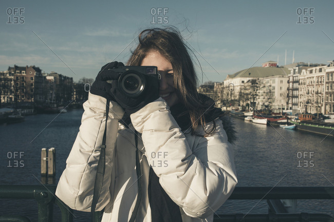 Smiling young woman photographing with camera against canal in city