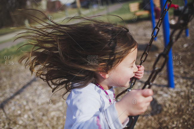 Side view of playful girl swinging at playground
