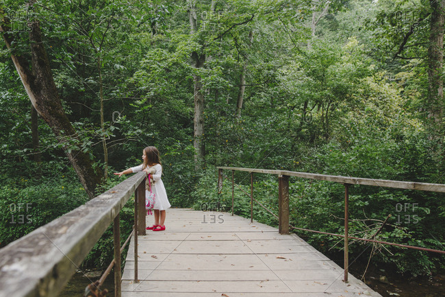 Full length of carefree girl standing on wooden footbridge at forest