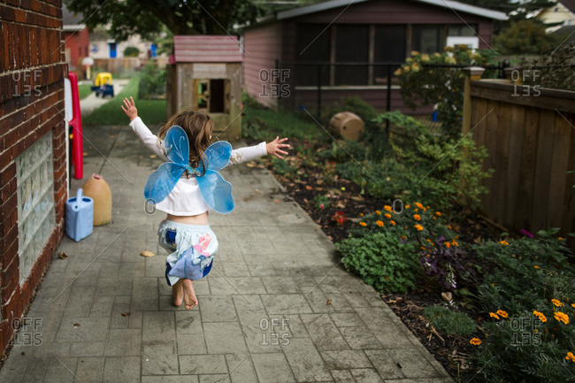 Rear view of playful girl wearing costume wings while running at backyard