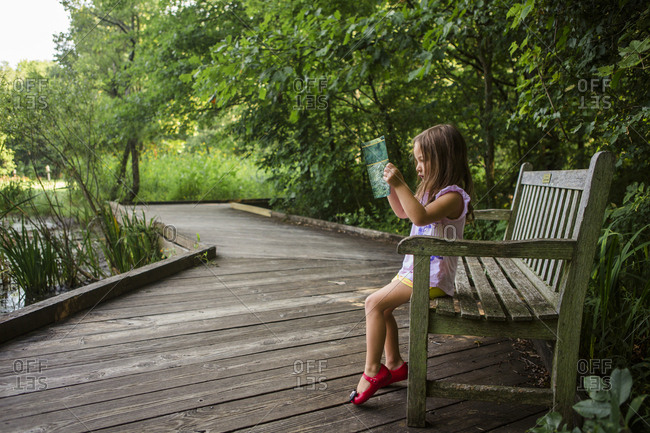 Side view of girl reading book while sitting on bench at park