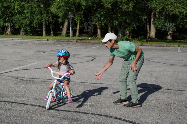 Father teaching daughter to ride bicycle at playground during sunny day