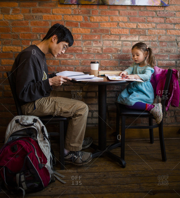 Father working while daughter reading book while sitting against brick wall at cafe