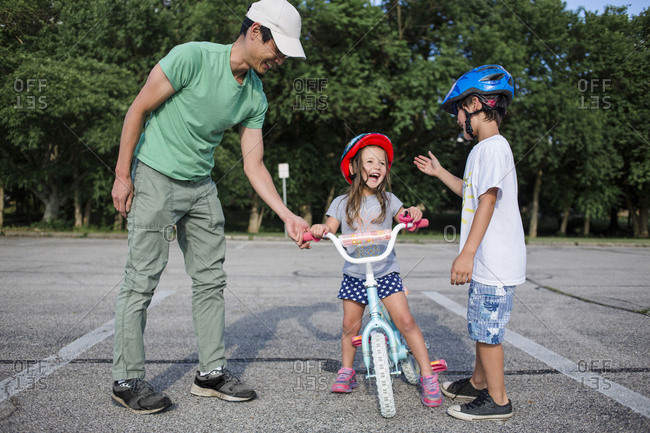 Cheerful girl learning cycling with father and brother at playground
